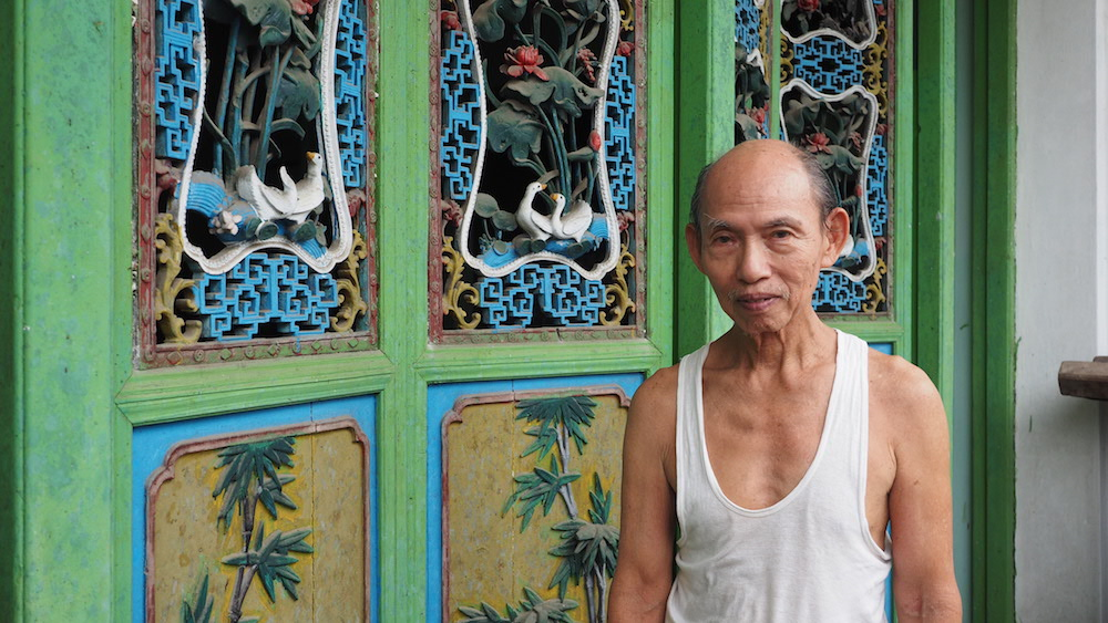 old man in front of green handcrafted door Yangon