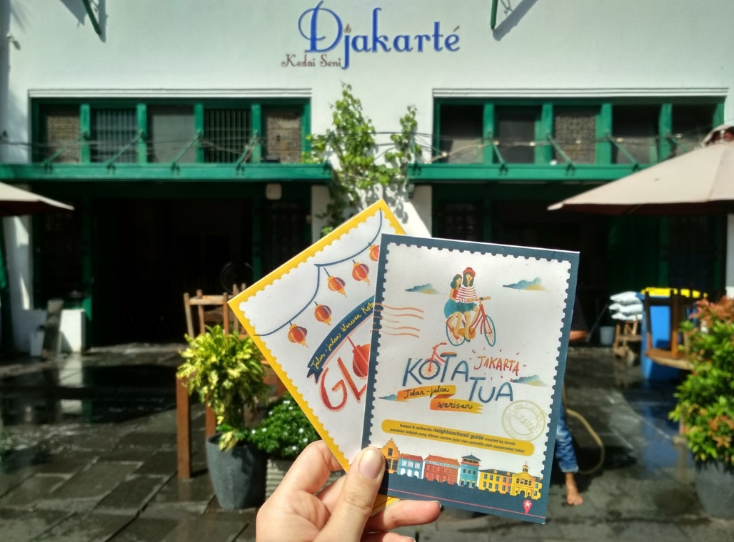 Someone holding two maps of cycling tours in Glodok and Kota Tua